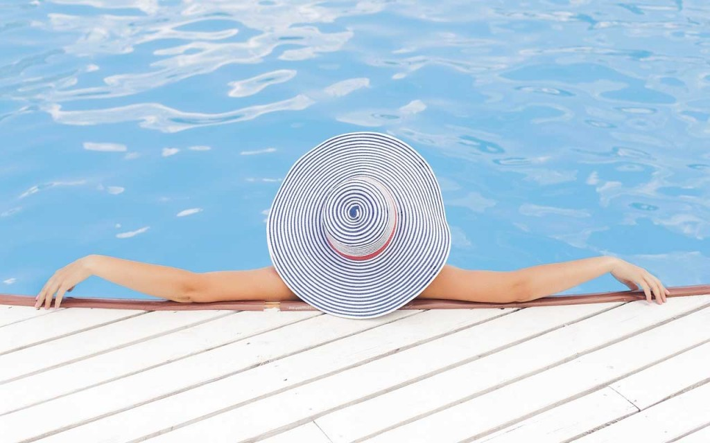 woman in hat sits in pool